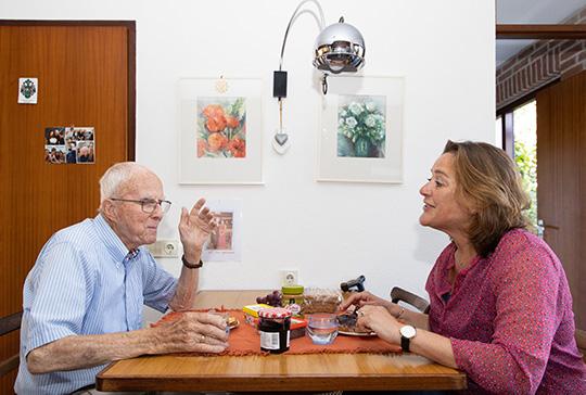 Ouderen en Saar zijn samen aan het eten en kletsen gezellig tijdens de maaltijd