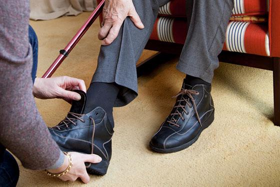 Saar ondersteunt ouderen met schoenen aantrekken